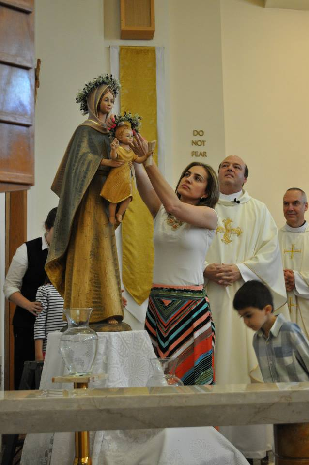 Gleisiany crowns baby Jesus as Fr. Michael and Fr. Ed and her son Antony look on.